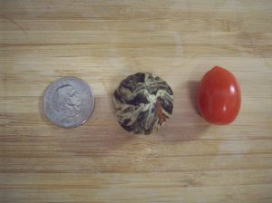 Size comparison, from left to right: a U.S. silver dollar, a Oriental Beauty tea ball, and a grape tomato / Photo courtesy of Sara Letourneau
